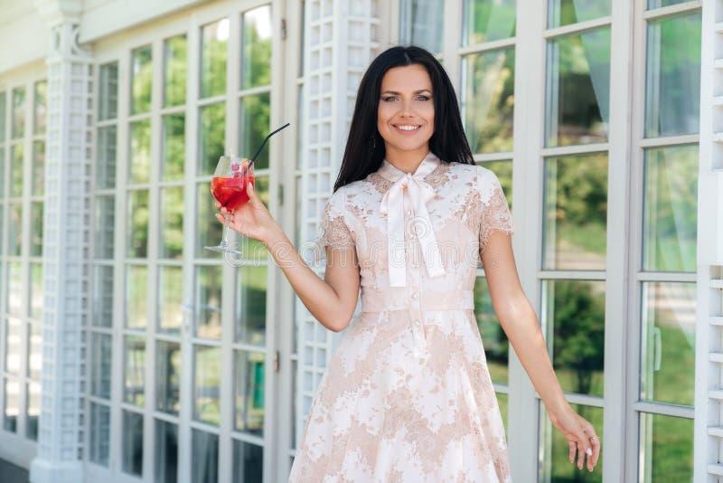 Menina moreno de sorriso com o vidro da limonada que levanta no vestido bege da cor fora do café perto de uma parede de madeira e fotografia de stock