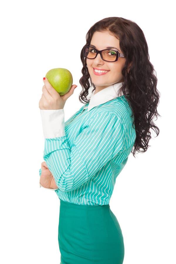 Menina moreno de sorriso na saia verde e na blusa que guardam a maçã fotos de stock