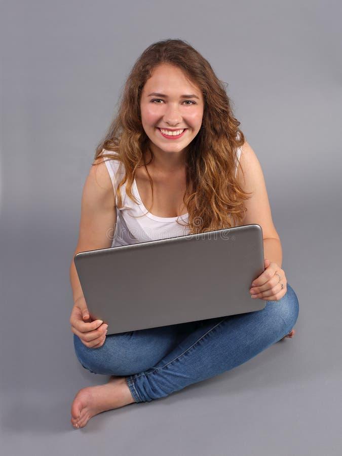 Menina moreno de sorriso que usa o portátil imagem de stock royalty free