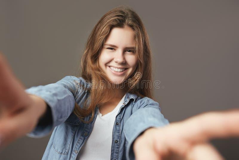 A menina moreno de sorriso vestida em um t-shirt e em uma camisa brancos das calças de brim faz um selfie em um fundo cinzento imagens de stock