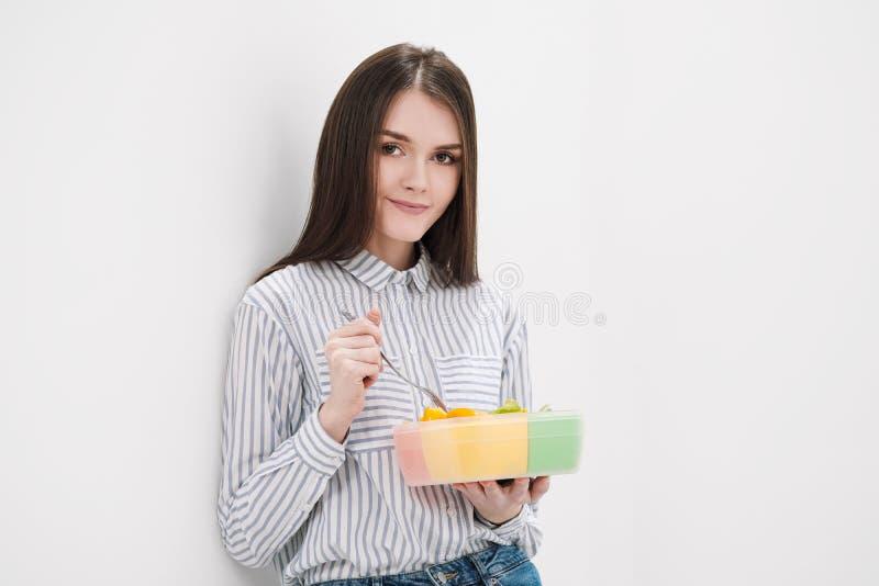 A menina moreno delgada com cabelo longo em um fundo branco come com uma forquilha de um recipiente para almoços Caixa de cor par imagem de stock