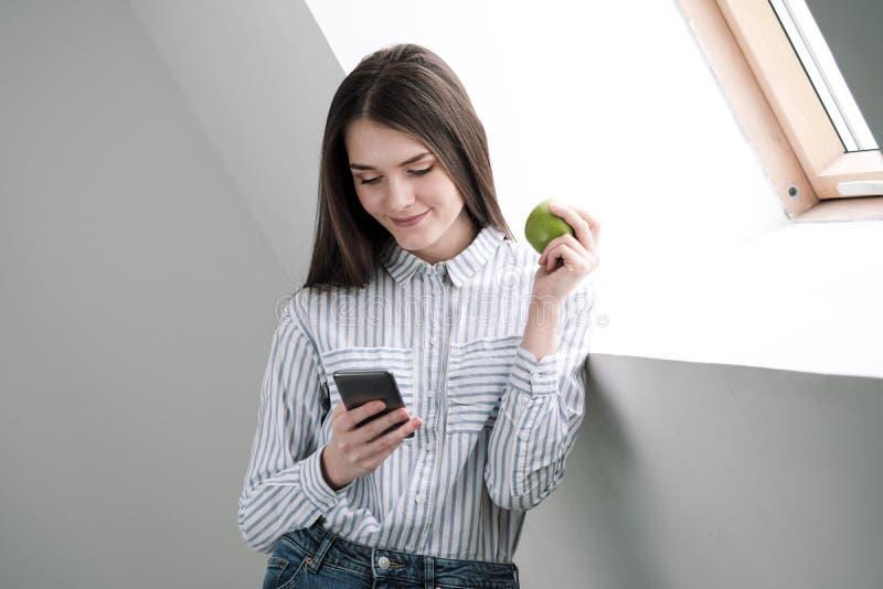 Menina moreno delgada com cabelo longo em um fundo branco perto da janela do escritório Usa um smartphone e a conversa e fotografia de stock royalty free