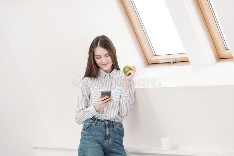 Menina moreno delgada com cabelo longo em um fundo branco perto da janela do escritório Usa um smartphone e a conversa e imagens de stock