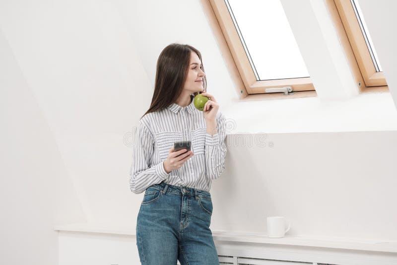Menina moreno delgada com cabelo longo em um fundo branco perto da janela do escritório Usa um smartphone e a conversa e fotografia de stock