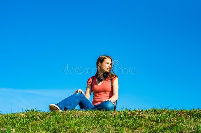 A menina moreno do adolescente no t-shirt coral com cabelo longo senta-se na grama no fundo do c?u com espa?o da c?pia imagens de stock royalty free