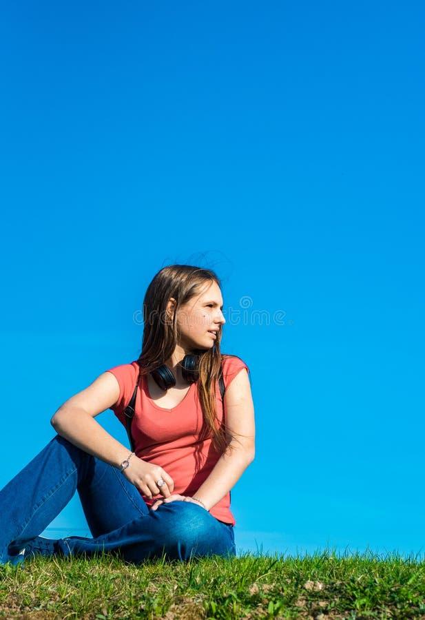 A menina moreno do adolescente no t-shirt coral com cabelo longo senta-se na grama no fundo do c?u com espa?o da c?pia fotos de stock royalty free