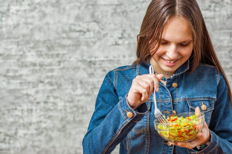 Menina moreno do adolescente novo com cabelo longo que come a salada verde dos vegetais no fundo cinzento da parede com espaço da fotografia de stock
