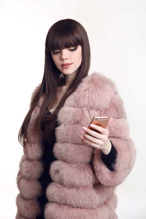 Menina moreno elegante no casaco de pele cor-de-rosa que guarda o telefone celular fotografia de stock