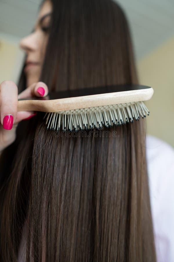 A menina moreno em uma camisa cor-de-rosa está penteando seu pente longo bonito do cabelo imagem de stock royalty free