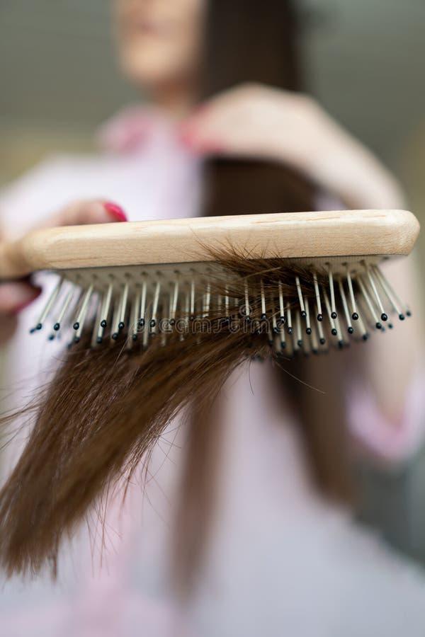 A menina moreno em uma camisa cor-de-rosa está penteando seu pente longo bonito do cabelo imagens de stock