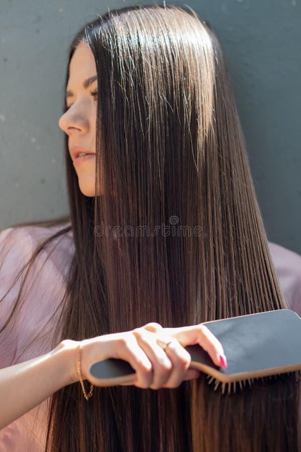A menina moreno em uma camisa cor-de-rosa está penteando seu pente longo bonito do cabelo imagens de stock royalty free