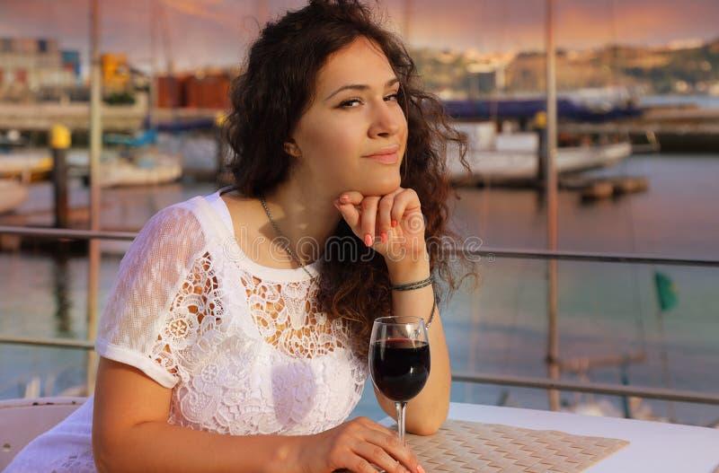 Menina moreno encantador com um vidro do vinho tinto foto de stock