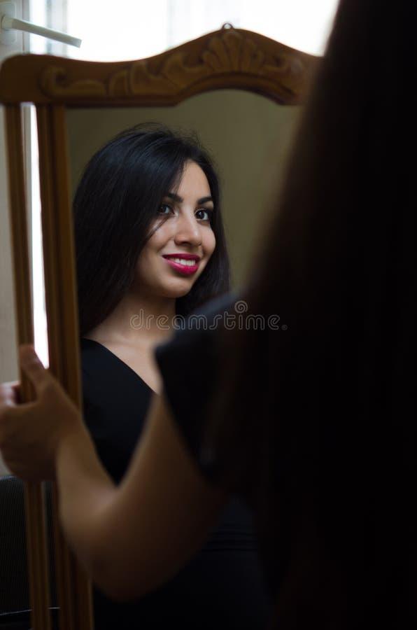 A menina moreno encantador nova olha sua reflexão no espelho foto de stock