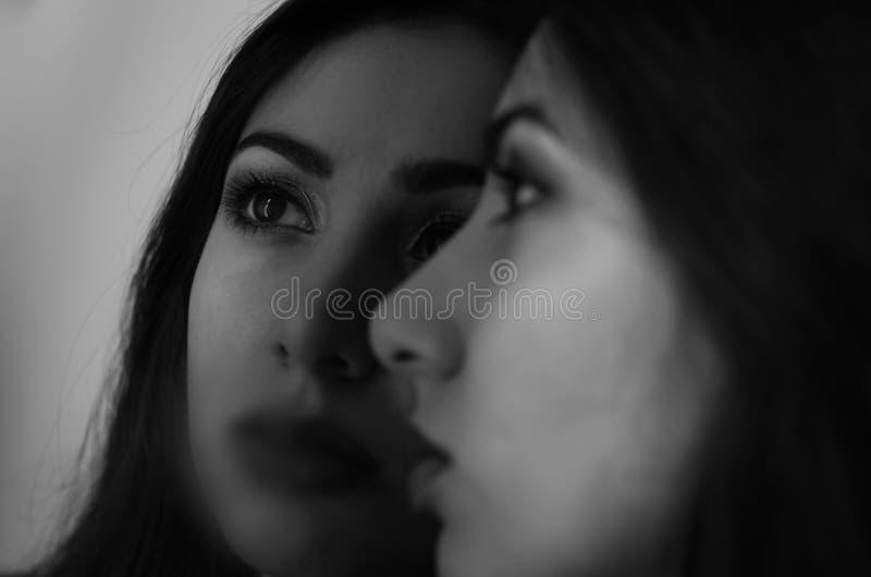 A menina moreno encantador nova olha sua reflexão no espelho imagem de stock royalty free