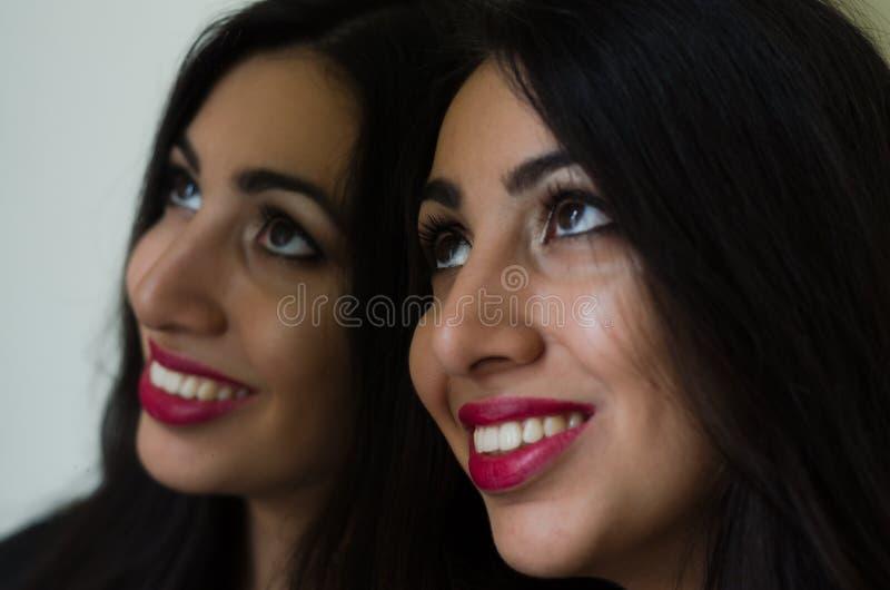 A menina moreno encantador nova olha sua reflexão no espelho foto de stock royalty free