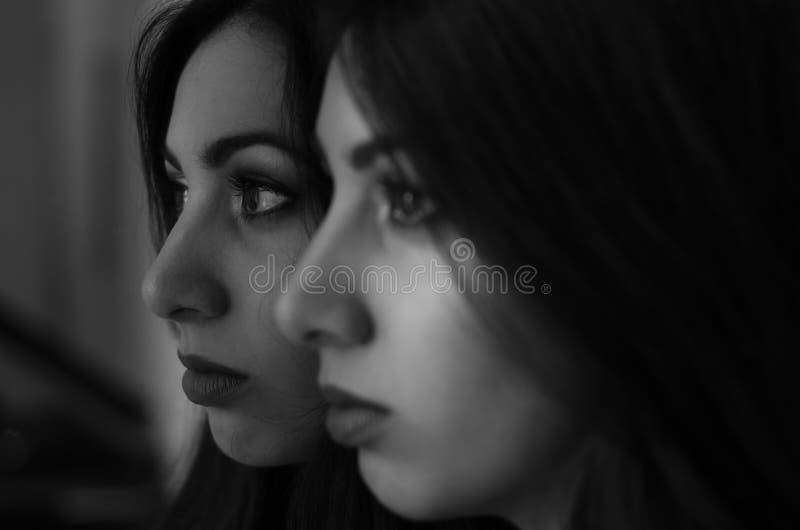 A menina moreno encantador nova olha sua reflexão no espelho imagens de stock royalty free