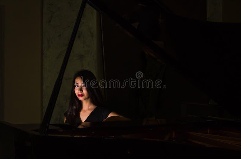 Menina moreno encantador nova que joga o piano fotografia de stock