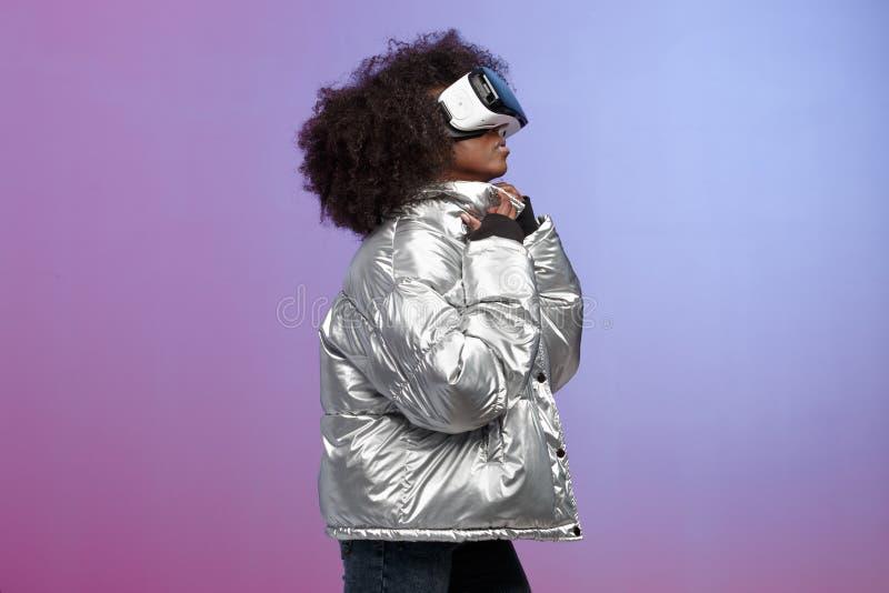 A menina moreno encaracolado na moda vestida em um revestimento prata-colorido usa os vidros da realidade virtual no est?dio no n imagem de stock
