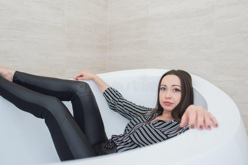 A menina moreno encontra-se em uma banheira com uma expressão calma e calma foto de stock royalty free