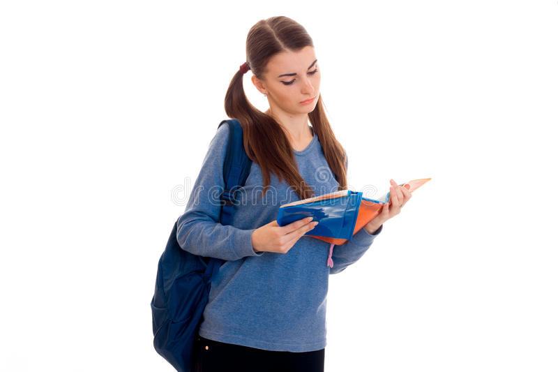 A menina moreno esperta nova do estudante com a trouxa em seus ombros lê um livro isolado no fundo branco fotografia de stock