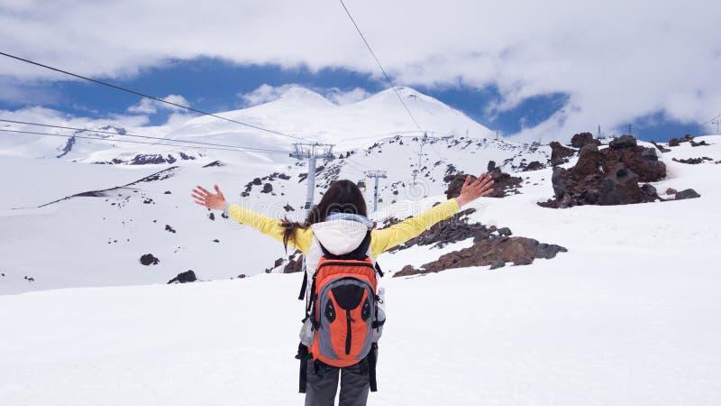 A menina moreno est? com sua parte traseira com uma trouxa em seus ombros com suas m?os aumentou e olhares para o Monte Elbrus imagem de stock royalty free