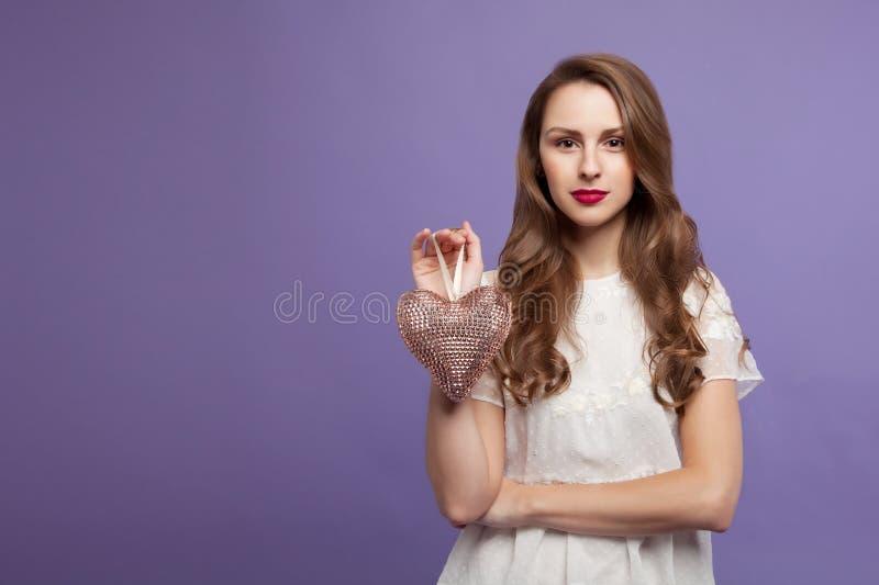 A menina moreno está guardando um coração decorativo em sua mão Em um fundo lilás Conceito para o dia do ` s do Valentim Lugar pa fotos de stock