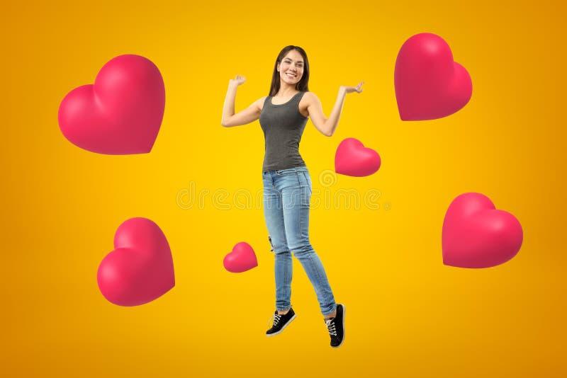 Menina moreno feliz nova que veste calças de brim e o t-shirt ocasionais com corações cor-de-rosa no fundo amarelo fotos de stock