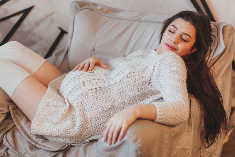 A menina moreno grávida em um branco fez malha a camiseta que encontra-se na poltrona imagens de stock royalty free