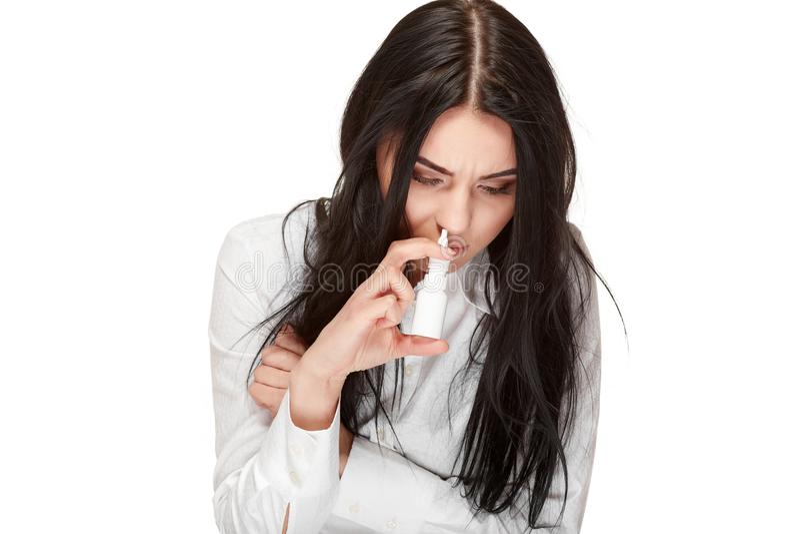 A menina moreno insalubre afoga o pulverizador para o anti vírus do nariz imagem de stock