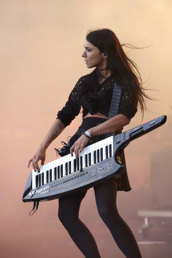 A menina moreno joga o sintetizador na fase durante um concerto de rocha imagens de stock
