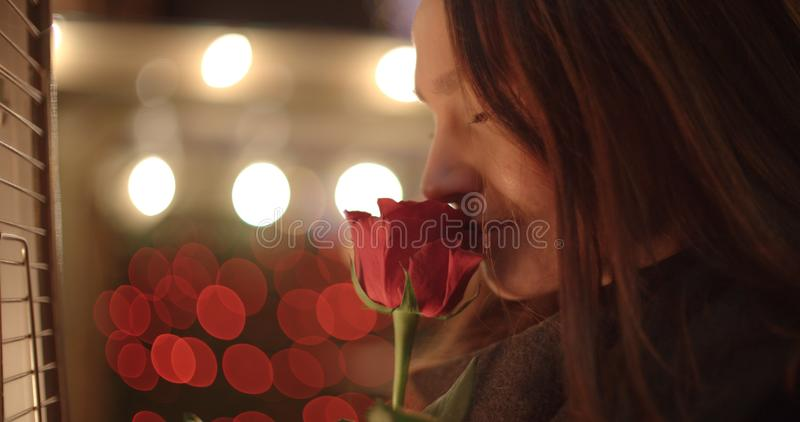 Menina moreno lindo em estar com rosa do vermelho em uma cidade imagem de stock royalty free