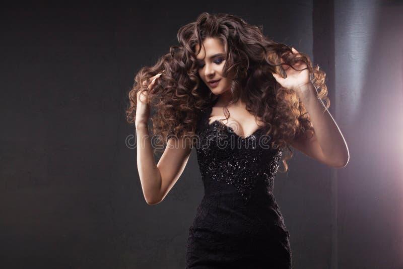 Menina moreno lindo no vestido preto elegante Cabelo curly longo bonito imagem de stock