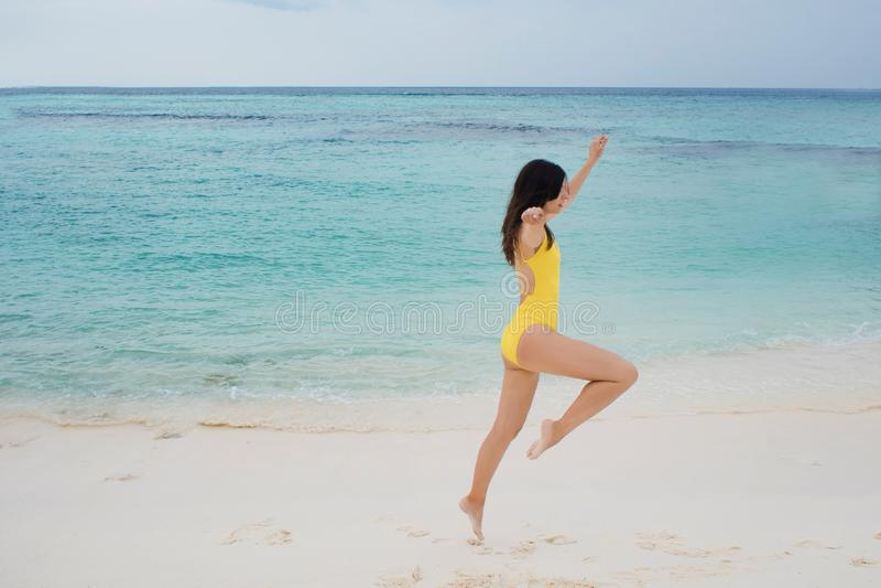 Menina moreno magro no roupa de banho amarelo que salta na praia imagens de stock