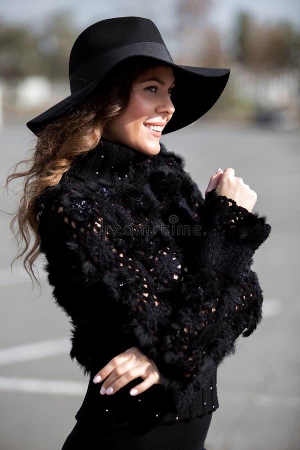Menina moreno ? moda de encantamento vestida em uma camiseta preta feita malha ? moda com pele, a saia preta e o chap?u elegante  fotografia de stock