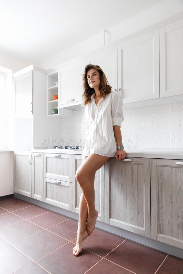 Menina moreno na camisa branca na cozinha foto de stock