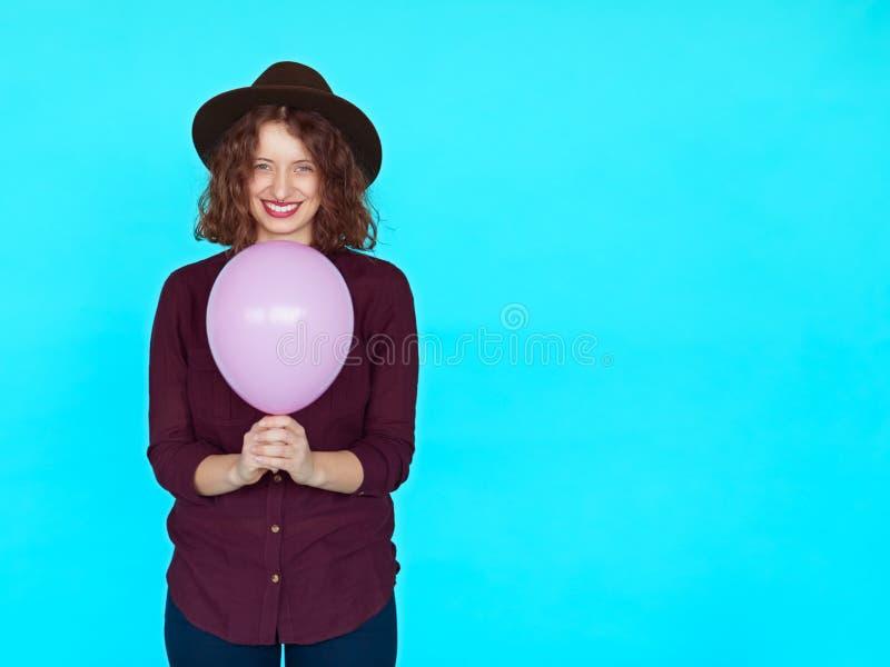 Menina moreno na moda que veste o chapéu à moda, guardando um balão cor-de-rosa imagem de stock