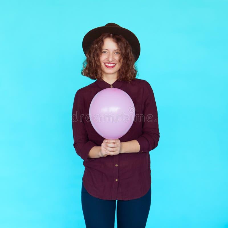 Menina moreno na moda que veste o chapéu à moda, guardando um balão cor-de-rosa imagens de stock royalty free