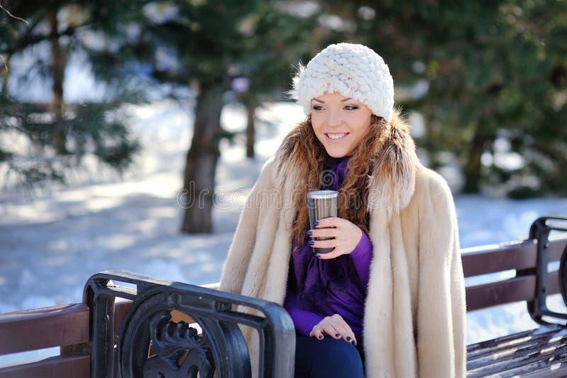 Menina moreno no chapéu branco que senta-se em um banco com um copo no inverno foto de stock