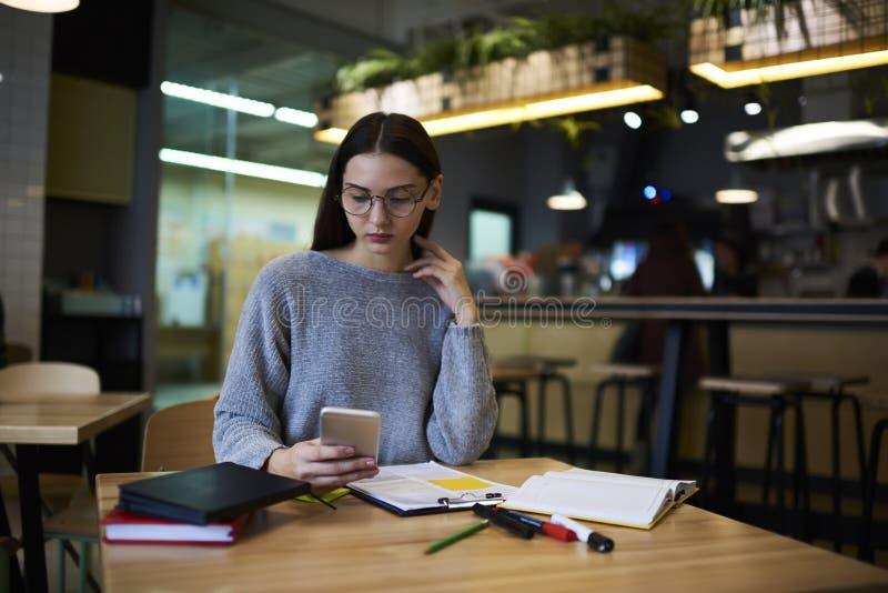 A menina moreno nos vidros executa o trabalho diário que envia arquivos com os originais através do smartphone conectado ao wifi fotos de stock royalty free