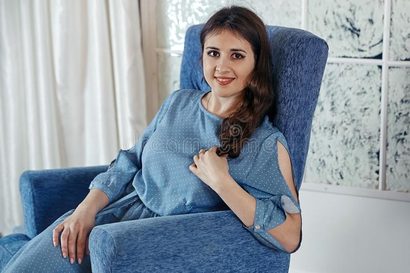 A menina moreno nova bonita em um vestido azul está sentando-se em um bl imagem de stock royalty free