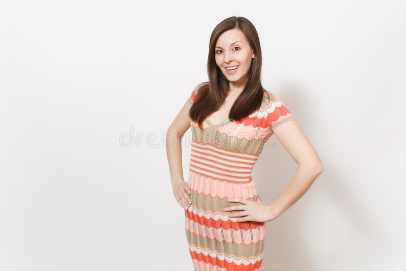 A menina moreno nova bonita no vestido modelado bege e cor-de-rosa leve exulta, sorrindo e guardando as mãos na cintura dentro fotografia de stock