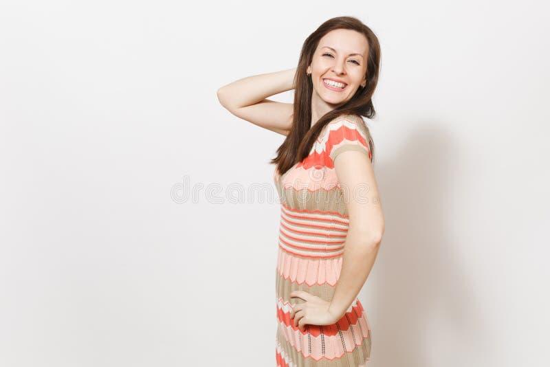 A menina moreno nova bonita no vestido modelado bege e cor-de-rosa leve que sorri, guarda a mão na cintura e perto da cabeça dent fotografia de stock