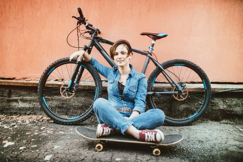 Menina moreno nova com o cabelo curto que está a bicicleta próxima do vintage e que guarda um skate, tendo o divertimento e um bo fotografia de stock royalty free