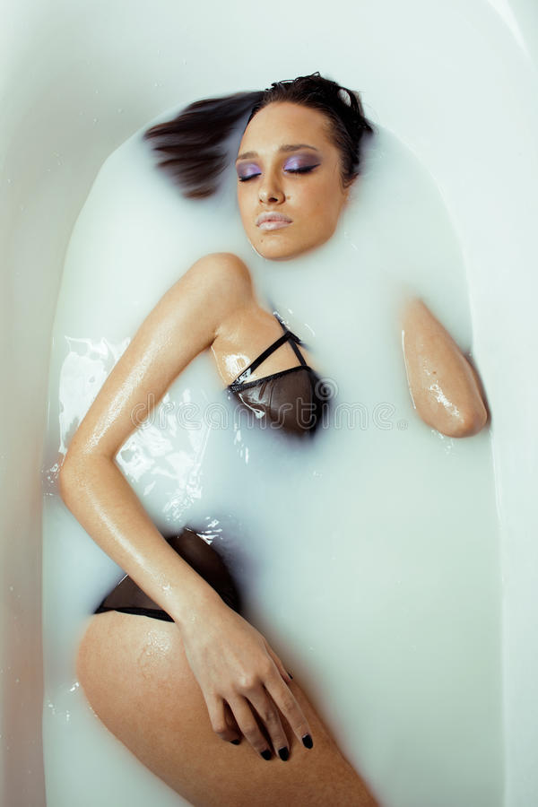 Menina moreno nova da beleza no banho, tomando termas do leite imagens de stock