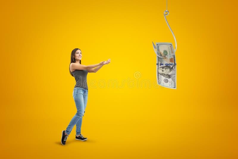 Menina moreno nova que veste calças de brim ocasionais e o t-shirt que guardam para fora suas mãos ao dólar do dinheiro no gancho fotos de stock