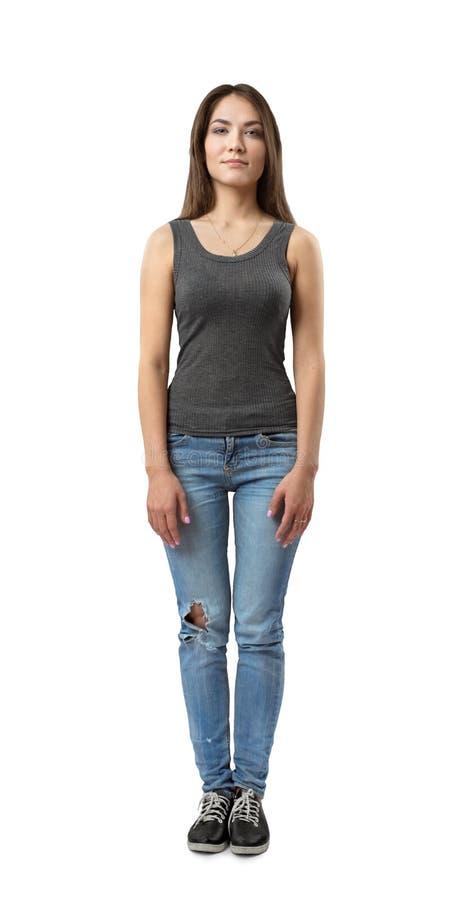 Menina moreno nova que veste calças de brim ocasionais e o t-shirt isolados no fundo branco foto de stock royalty free