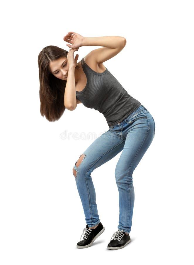 Menina moreno nova que veste calças de brim ocasionais e o t-shirt que protegem-se com as mãos isoladas no fundo branco imagens de stock royalty free