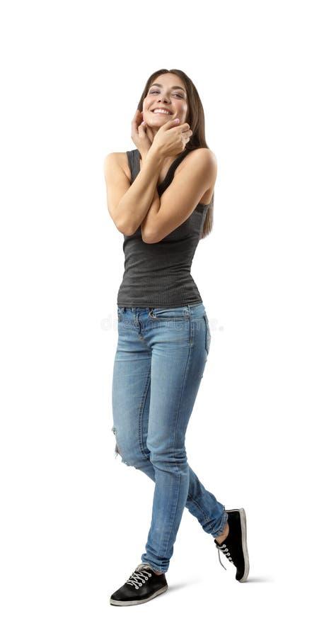 Menina moreno nova que vestem calças de brim ocasionais e sorriso do t-shirt e cara tocante isolada no fundo branco imagens de stock royalty free