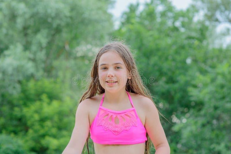 Menina moreno pequena bonita no maiô cor-de-rosa que senta-se na areia fotos de stock royalty free