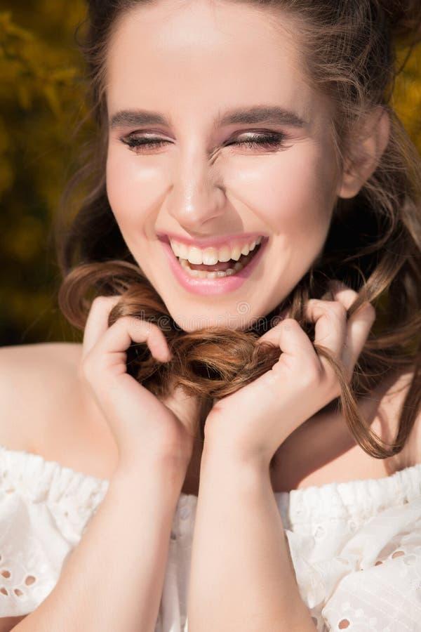 Menina moreno positiva com a composição bonita que levanta perto do blo fotografia de stock